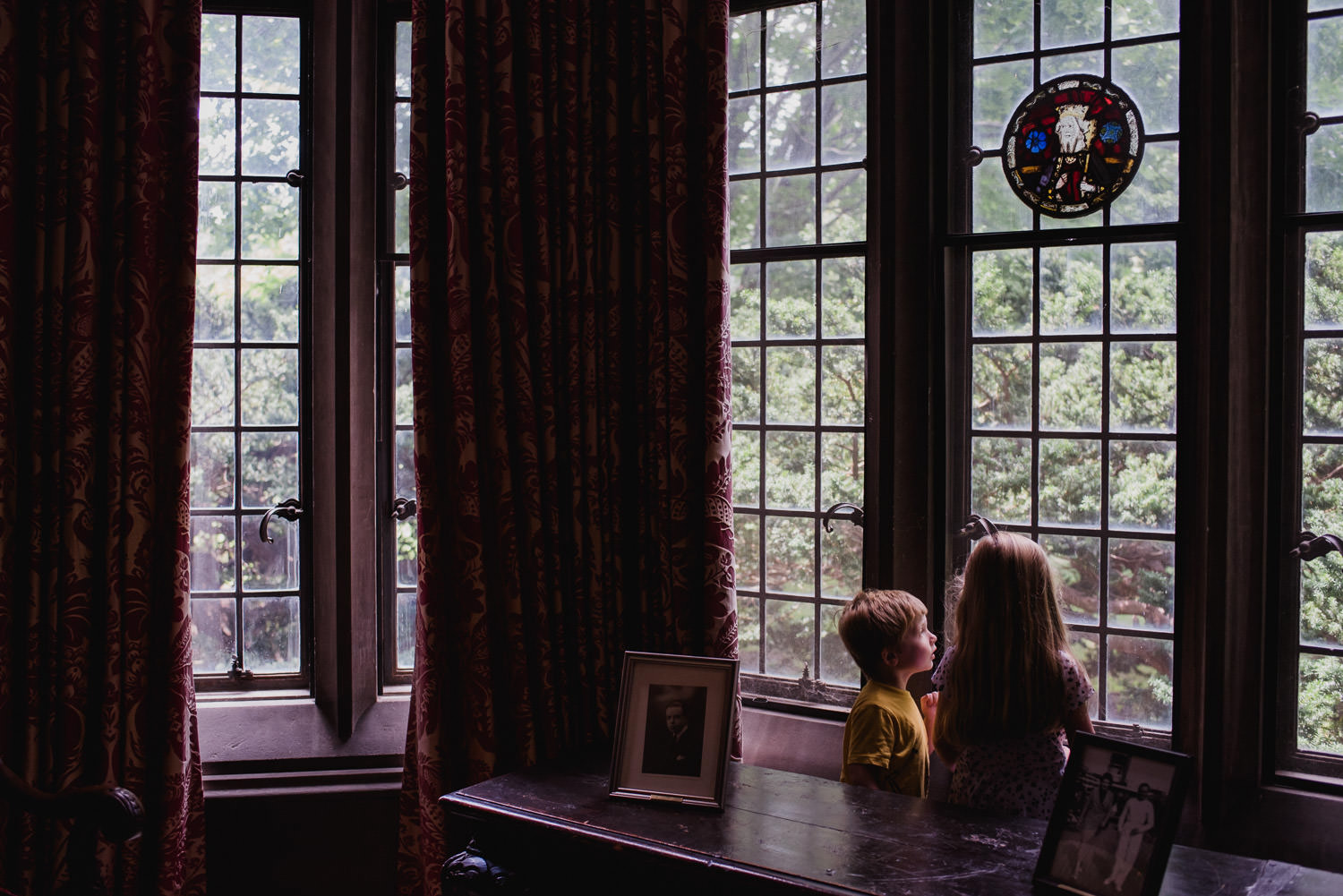 Two children look out a window at Coe House.