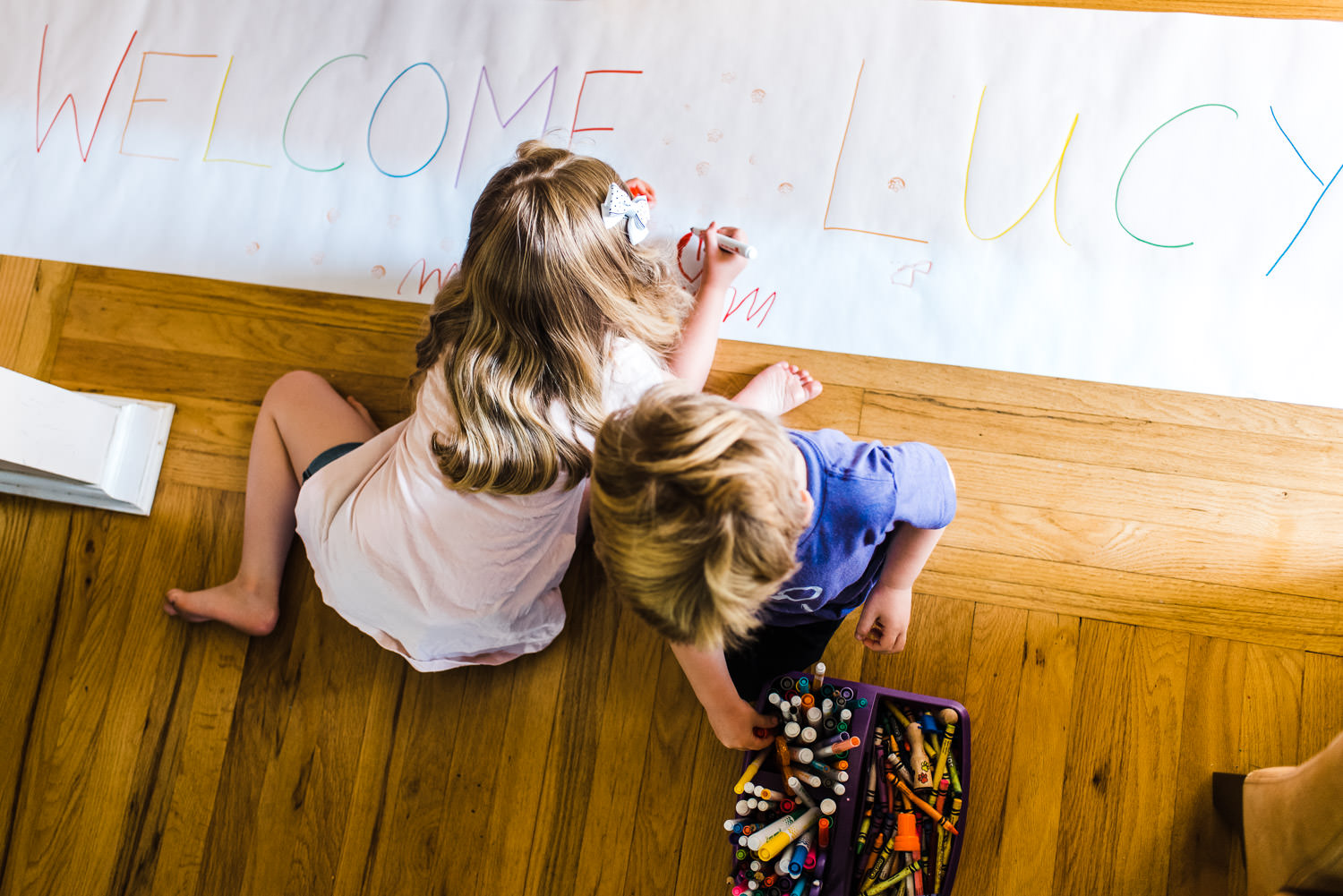 "A boy and girl make a ""welcome"" sign."