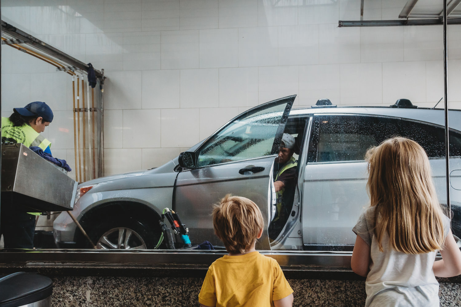 Two children watch their car get washed.