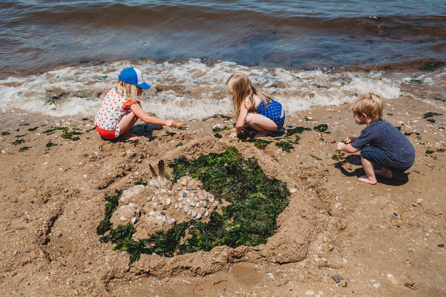 Three children build a sandcastle with seaweed and shells at Sands Point.