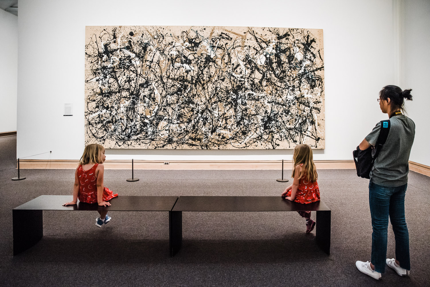 Two little girls sit and look at a Pollock painting at the Met.