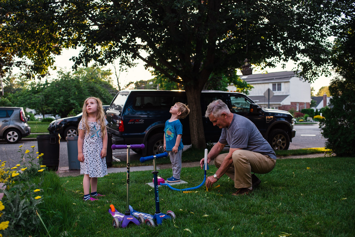 A grandfather helps his grandkids load a stomp rocket.