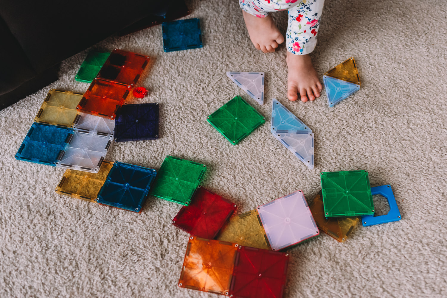 A child stands amidst a pile of Magna Tiles.