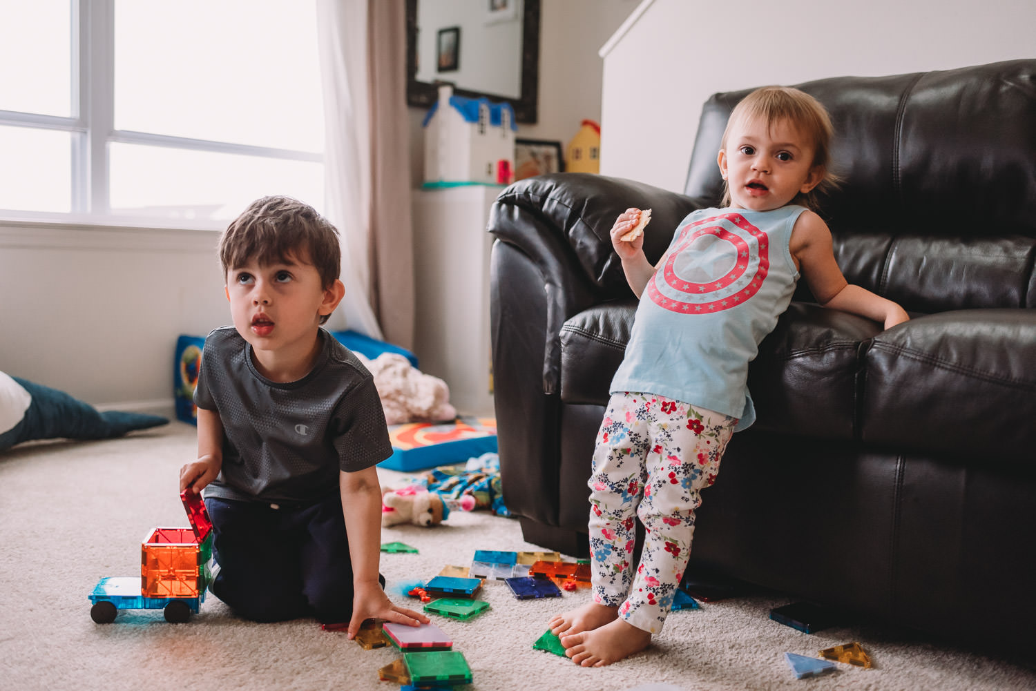 Two children play and watch TV in their living room.