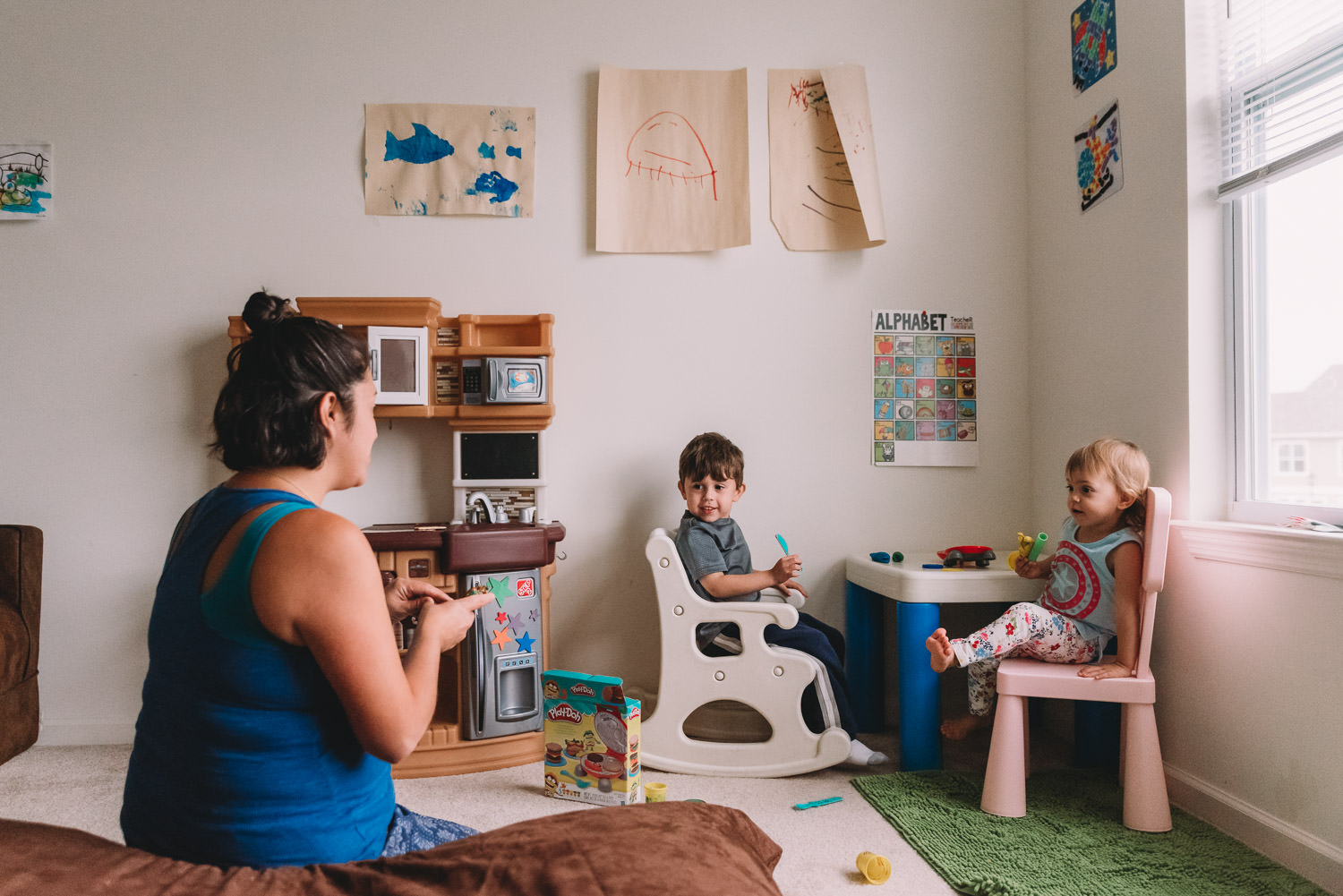 Children and their mom play in the playroom.