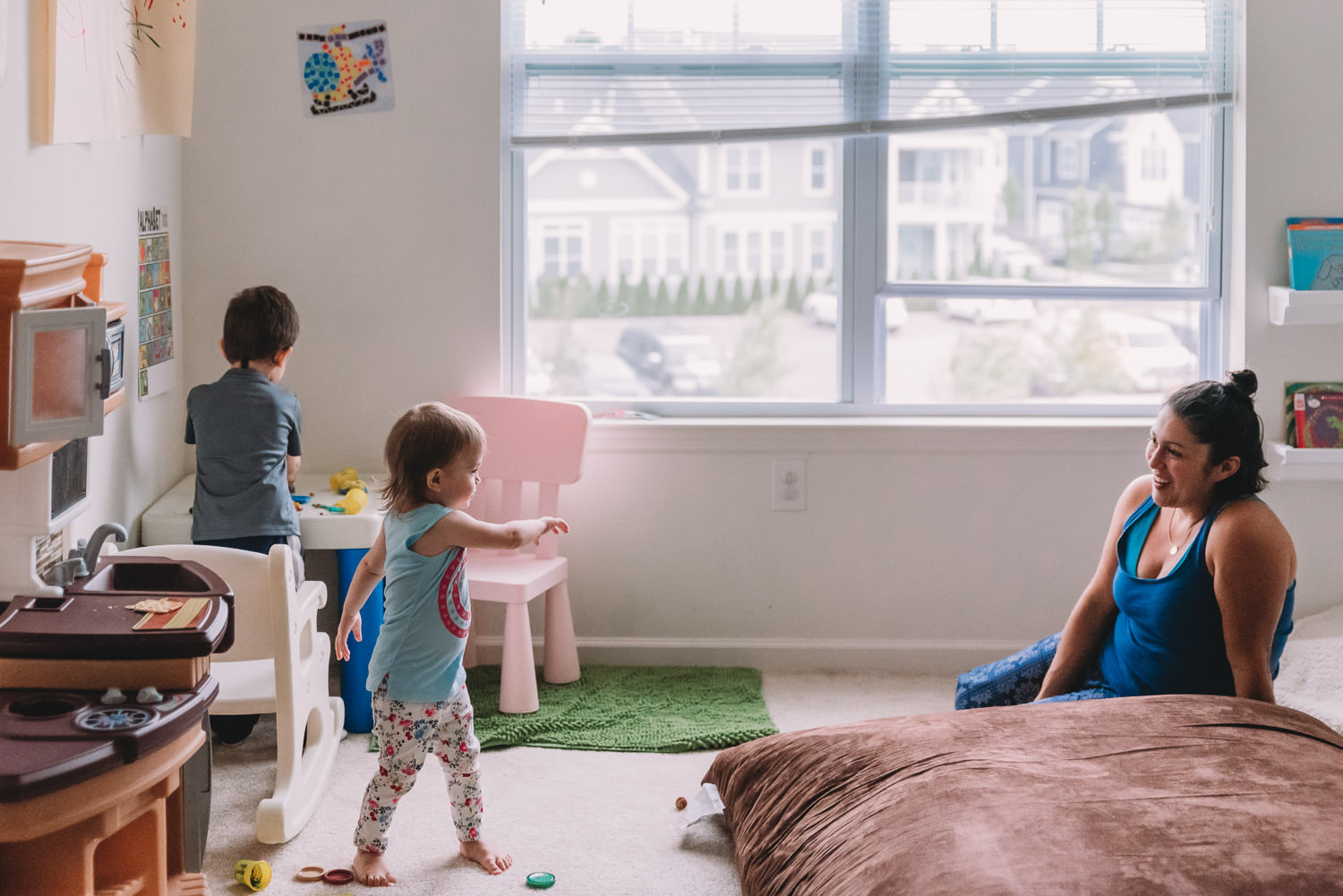 Kids and their mom play in a playroom.