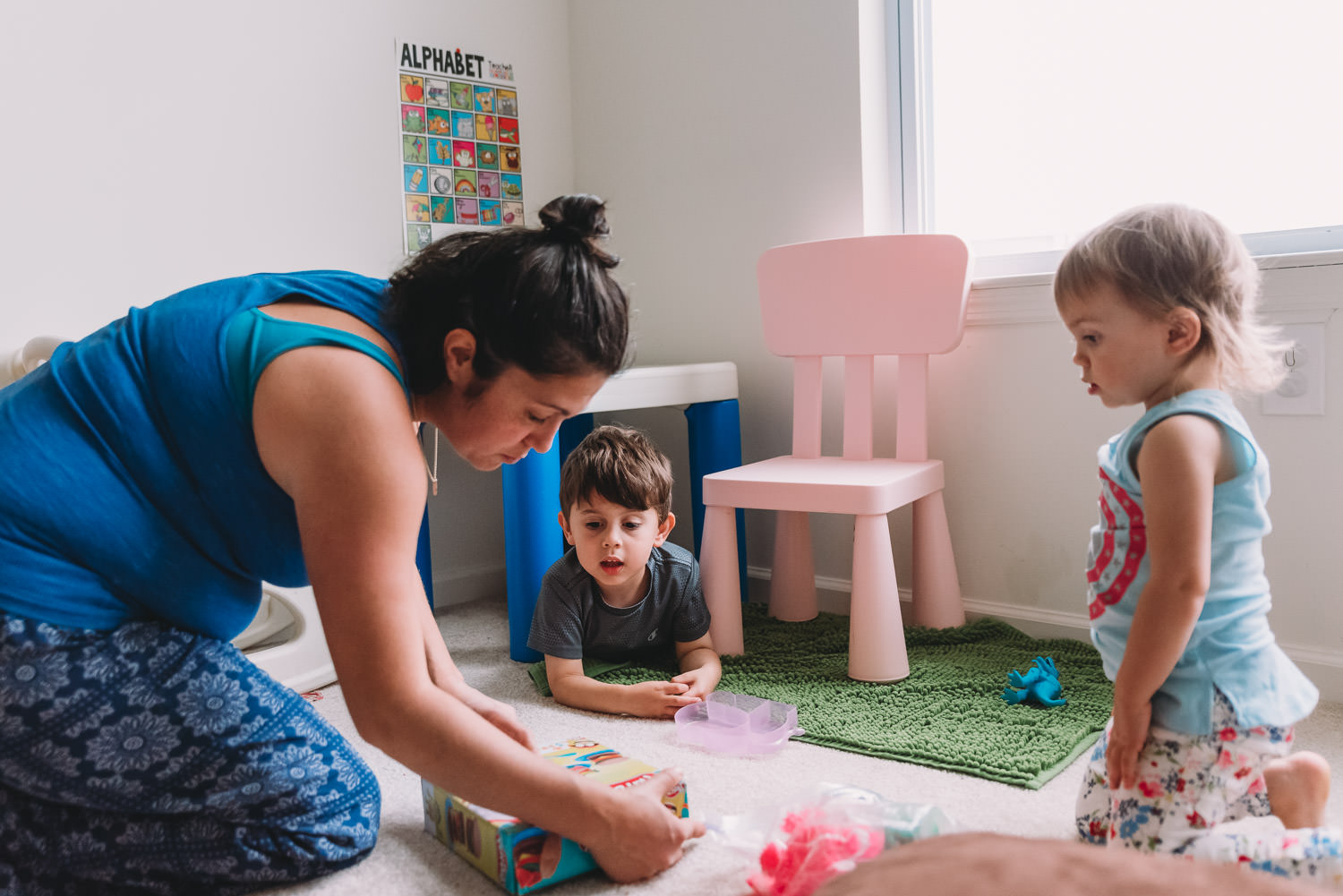 Two kids play with their mom in their playroom.