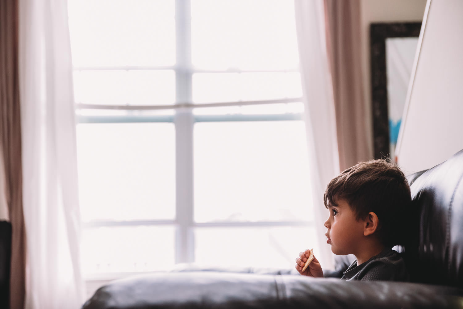 A little boy sits and eats a cracker while watching TV.