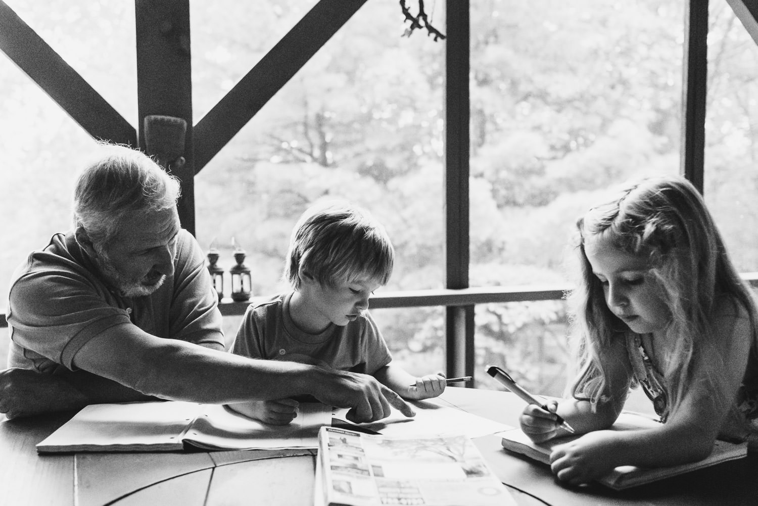 A grandfather works on homework with his grandkids on a screened-in porch.