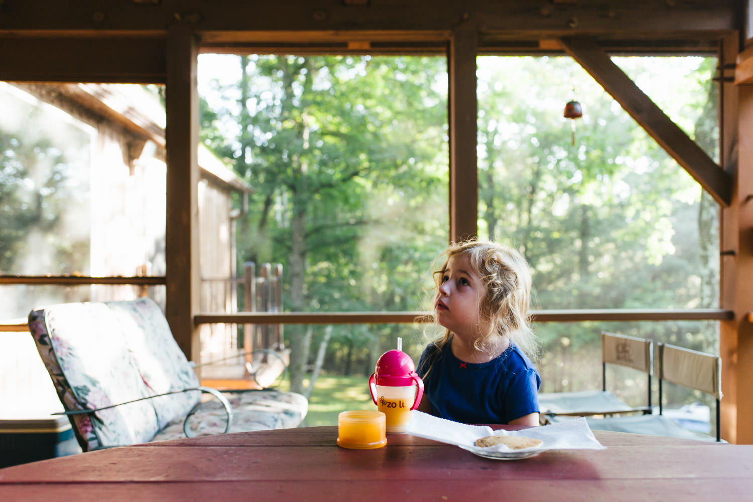 A little girl eats breakfast on a screened-in porch.