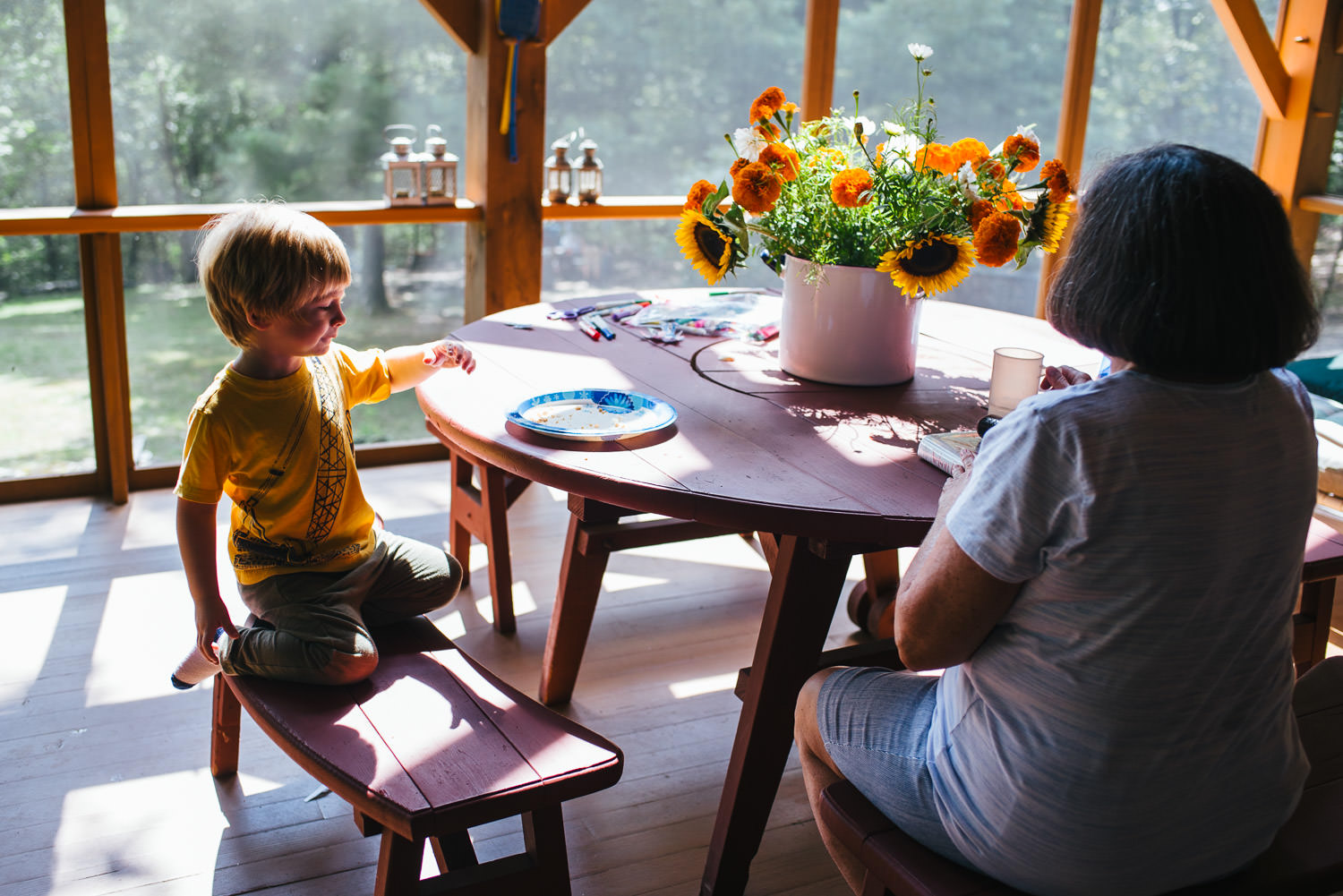 A little boy and his grandmother sit at a table with an arrangement of beautiful flowers.