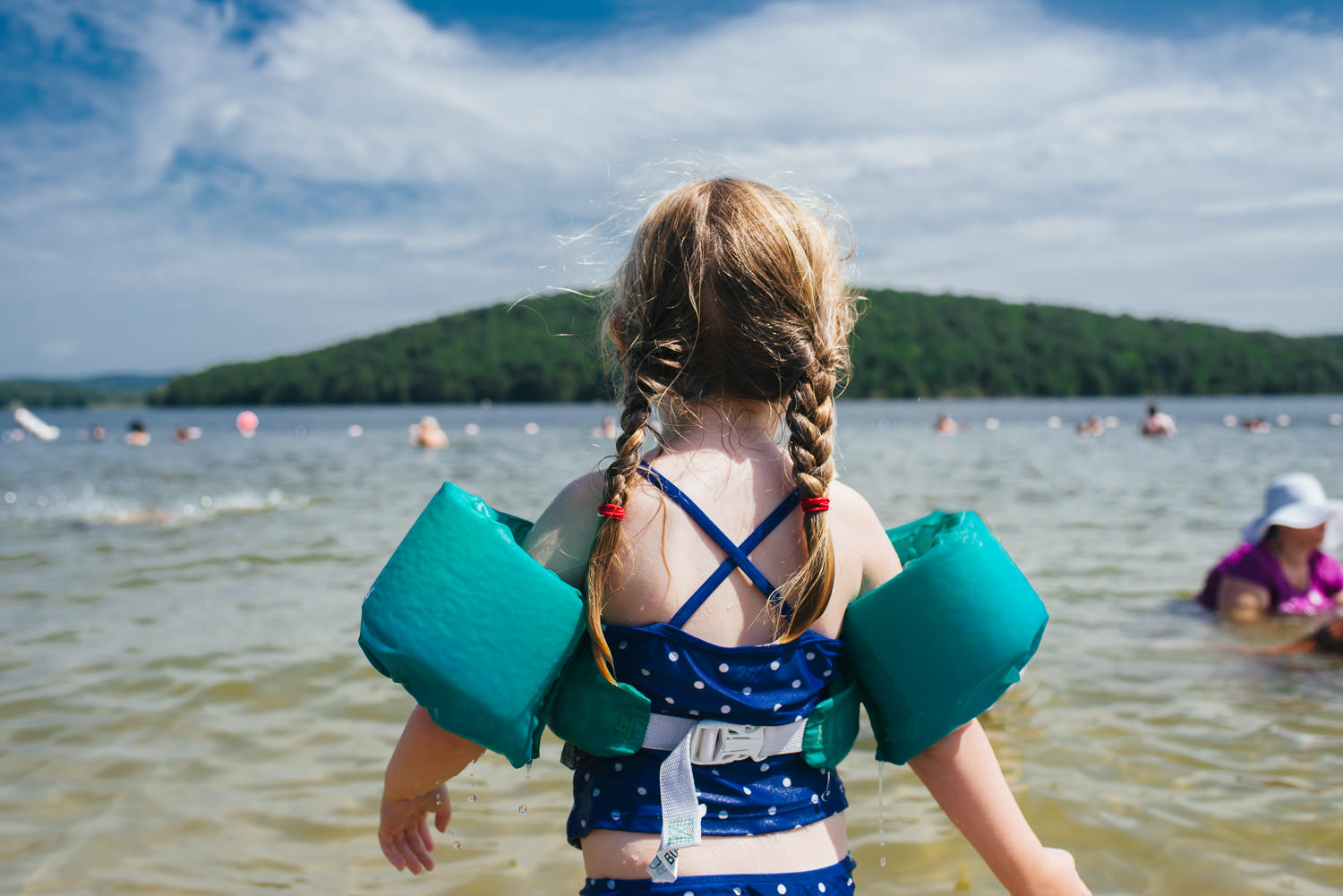 A little girl wearing swimmies looks out at the horizon at Lake Taghkanic.