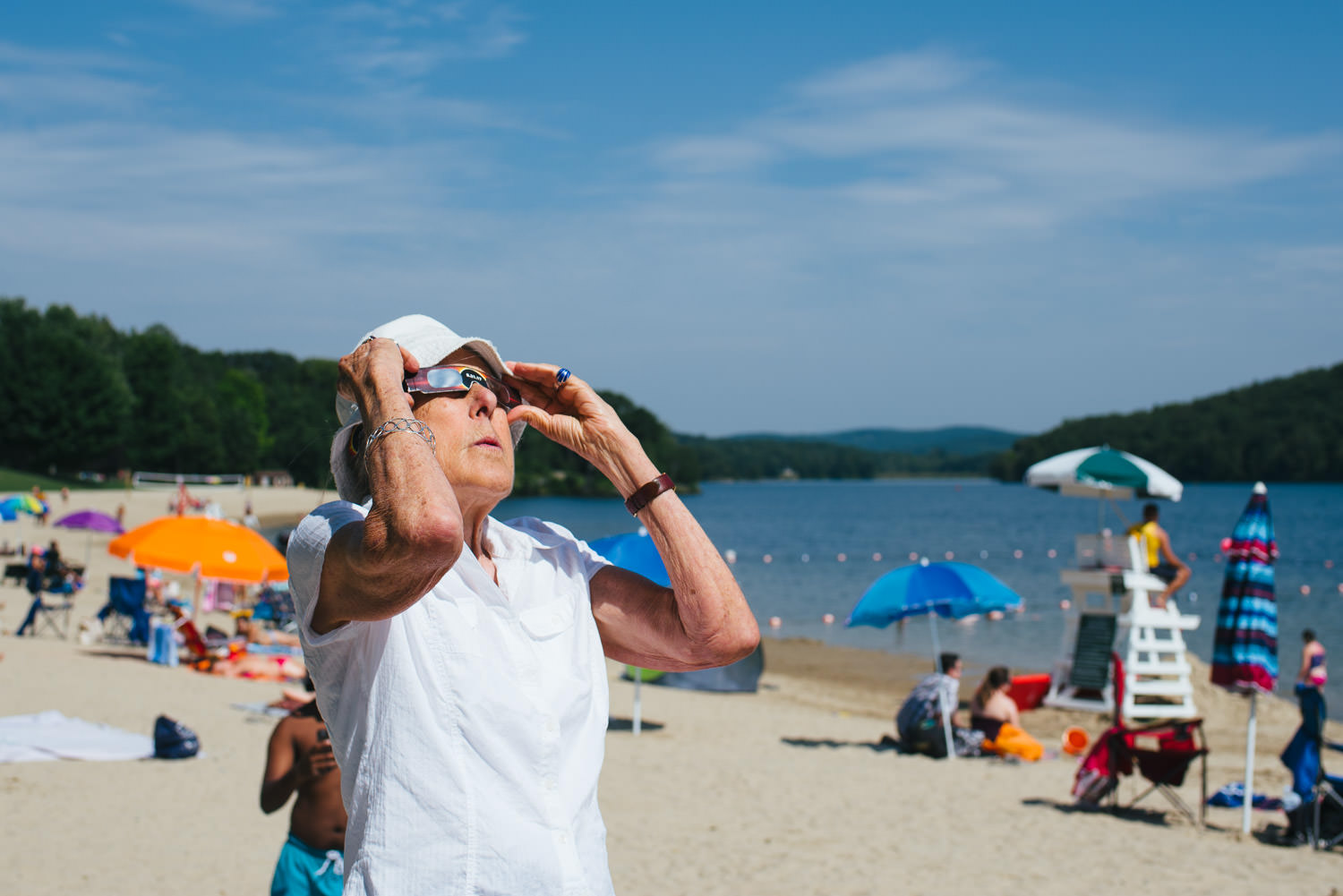 A lady looks at the eclipse through solar glasses.