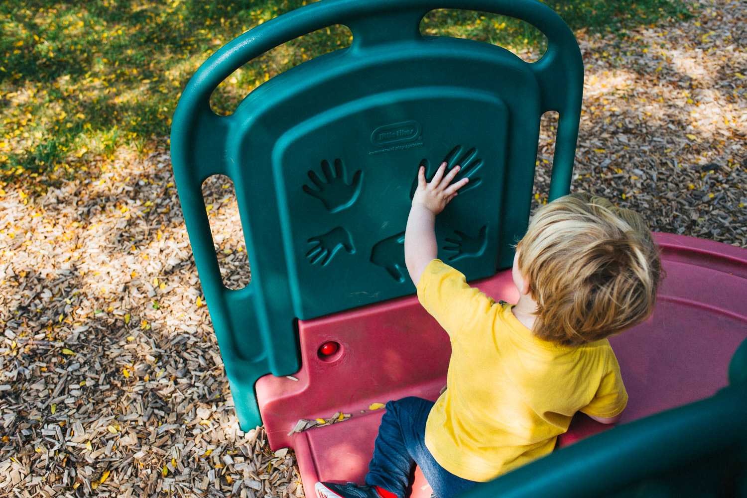 A little boy fits his hand into the imprint of a hand on some playground equipment.