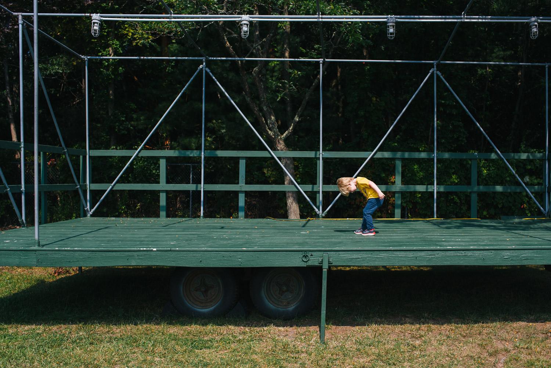 A little boy bows on a trailer.