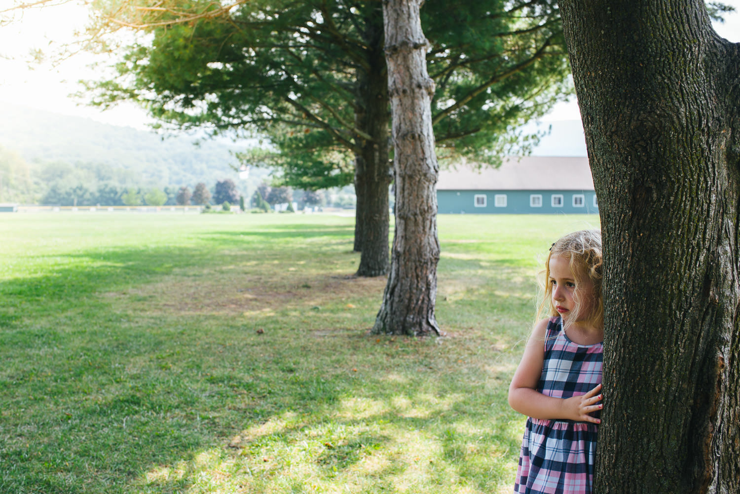 A little girl pouts next to a tree at the park.