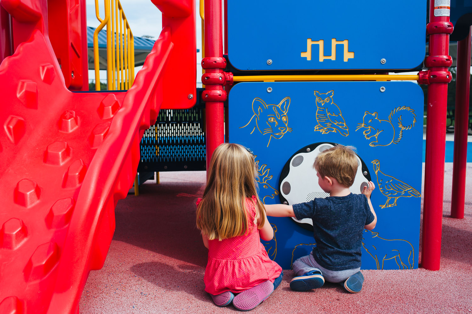Kids play at a brightly colored playground.