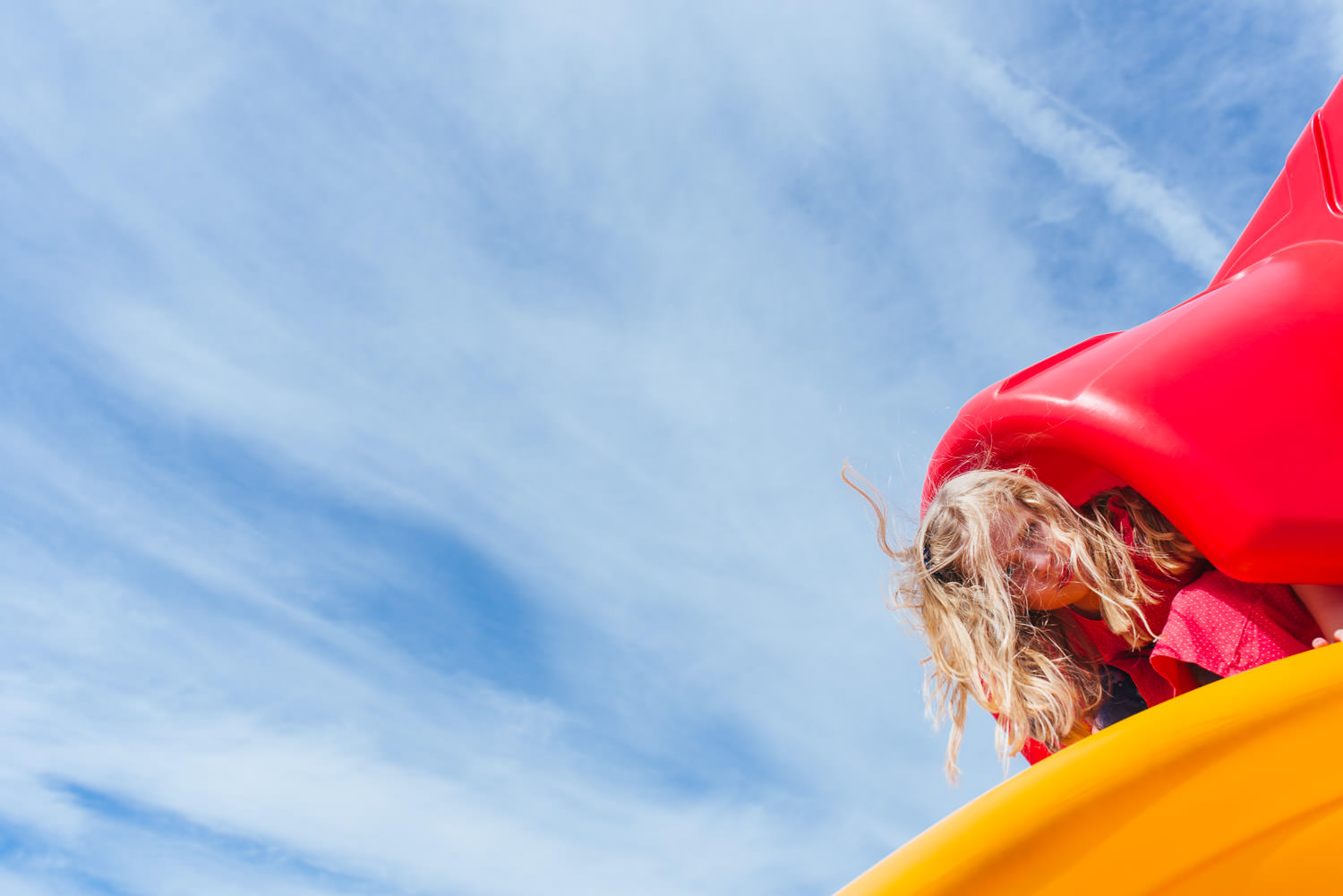 A little girl goes down a brightly colored slide.