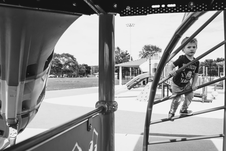 A little boy climbs a play structure at Eisenhower Park.