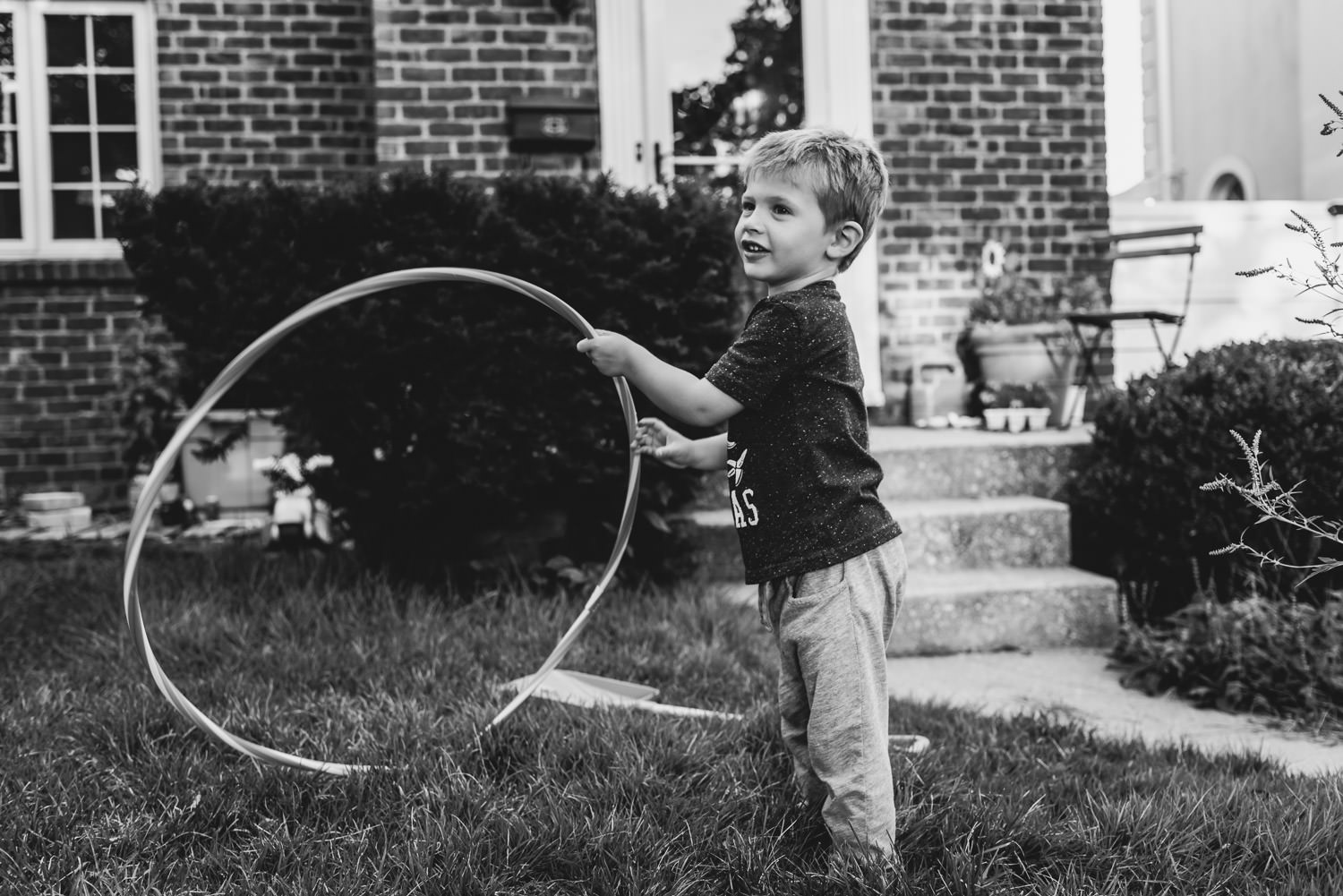 A little boy plays with a hula hoop in the yard.