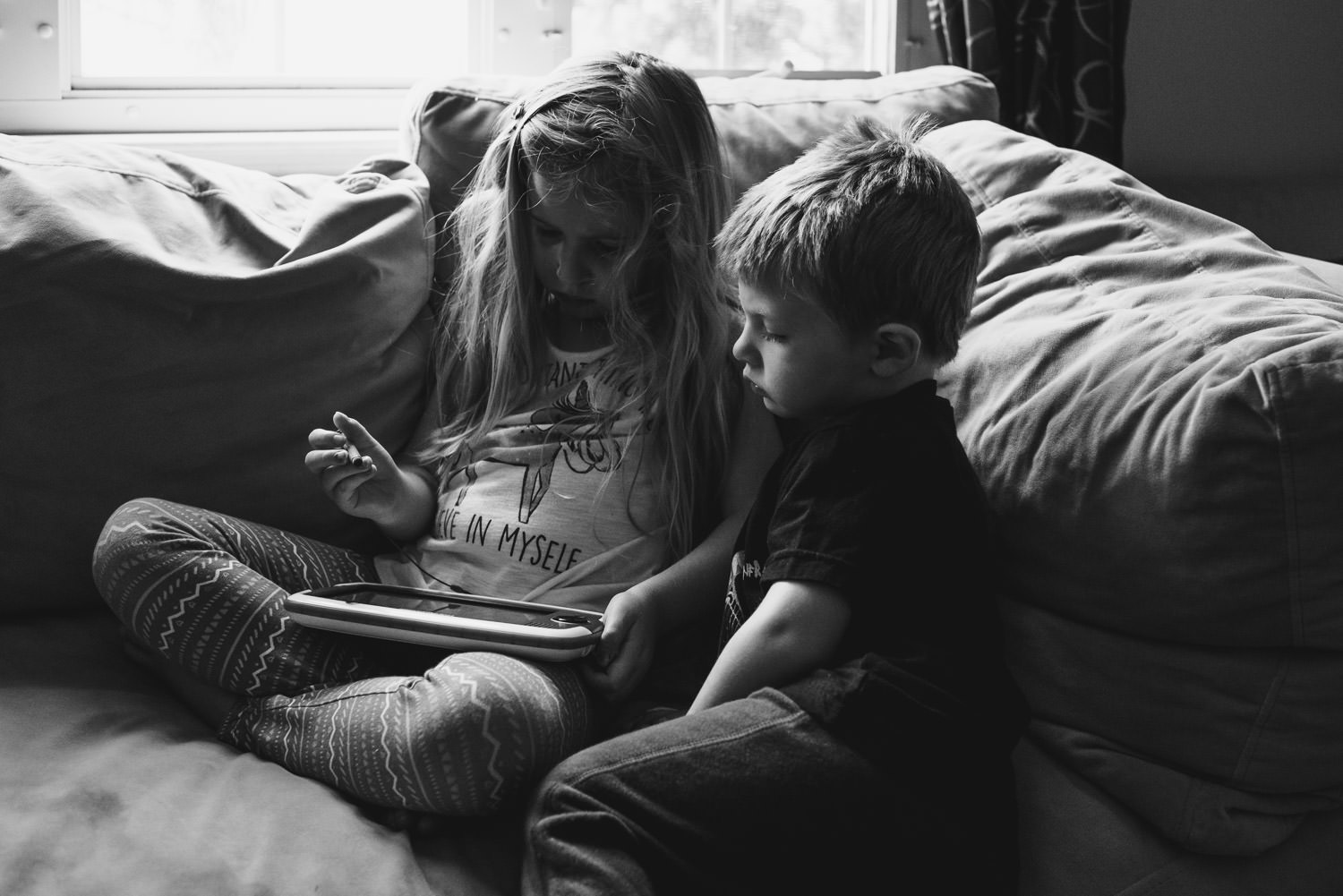 Two kids play with a Leappad on their living room couch.