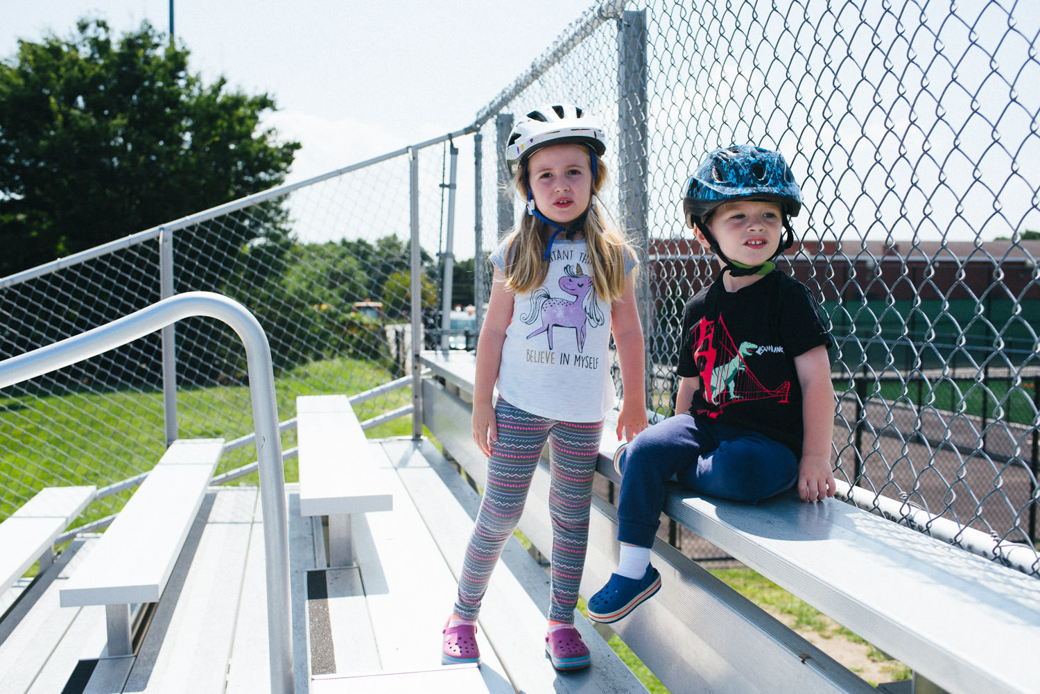 A brother and sister sit atop the bleachers.