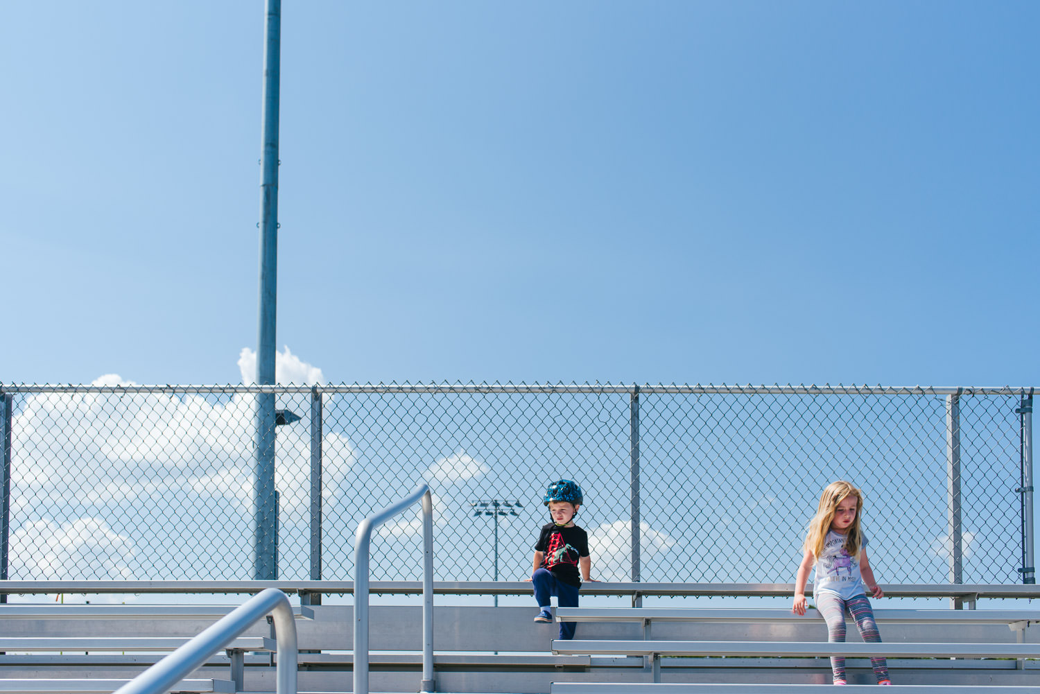 Kids sit at the top of a bank of bleachers.