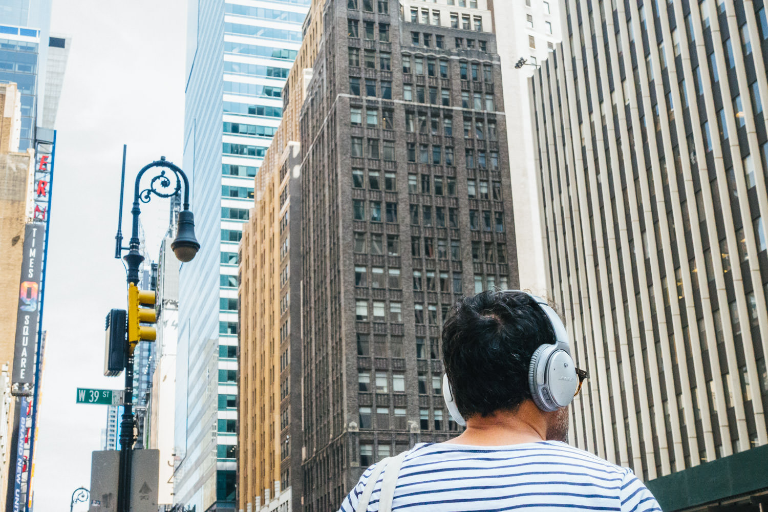 A man listens to headphones on the streets of NYC.