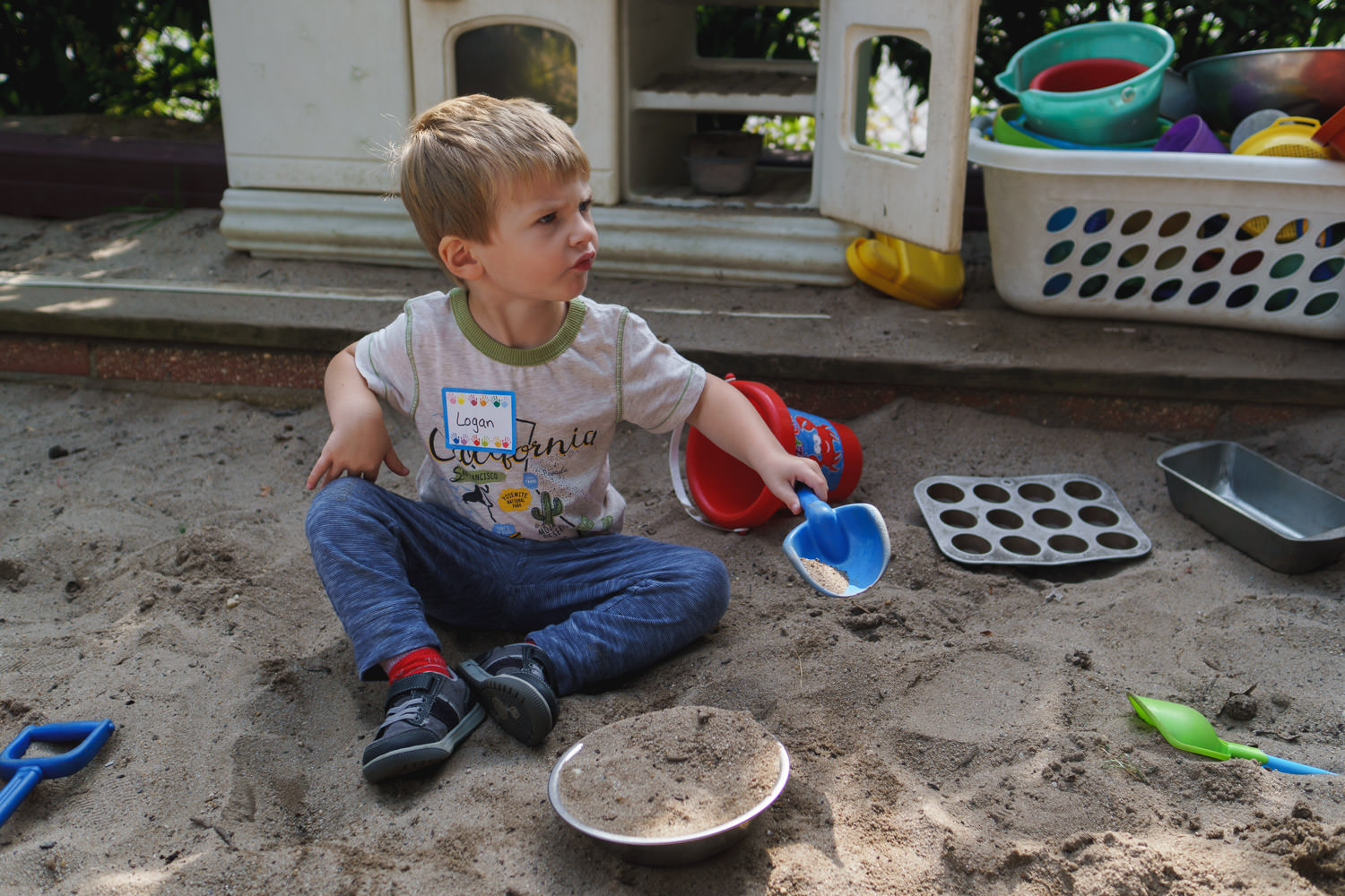 A little boy plays in a sandbox at preschool.