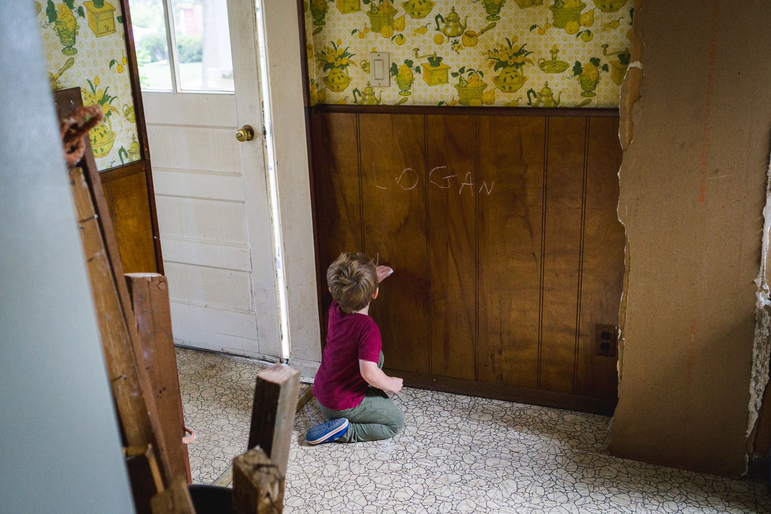 A little boy writes on the wall of an old house with some chalk.