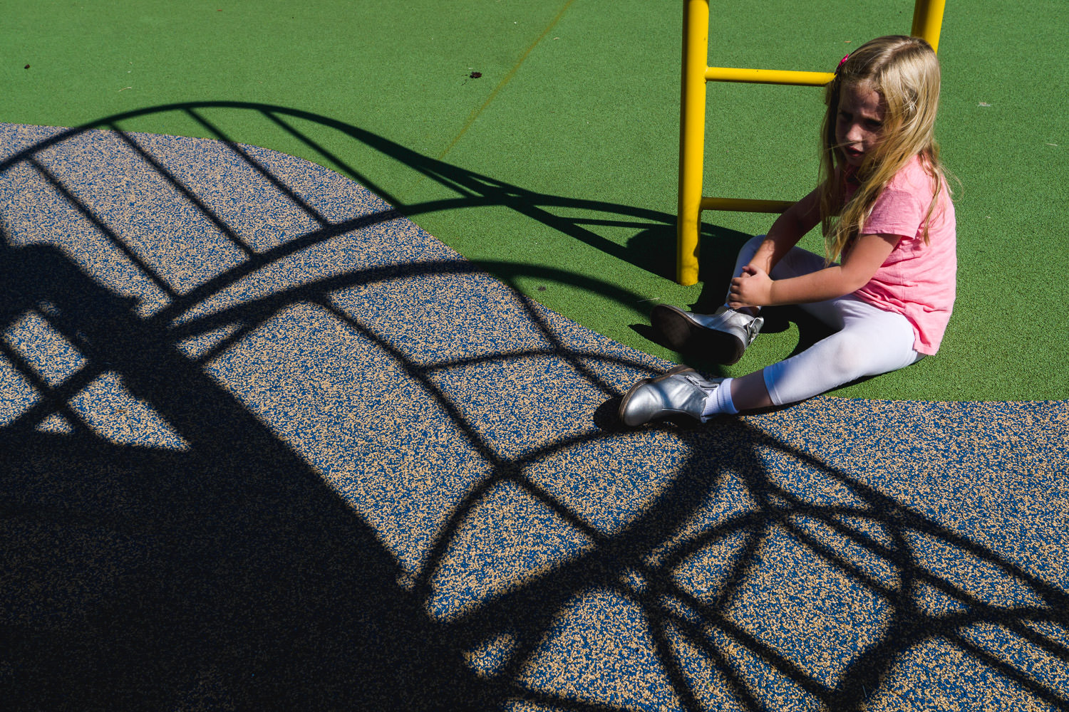 A little girl sits on the ground at the playground.
