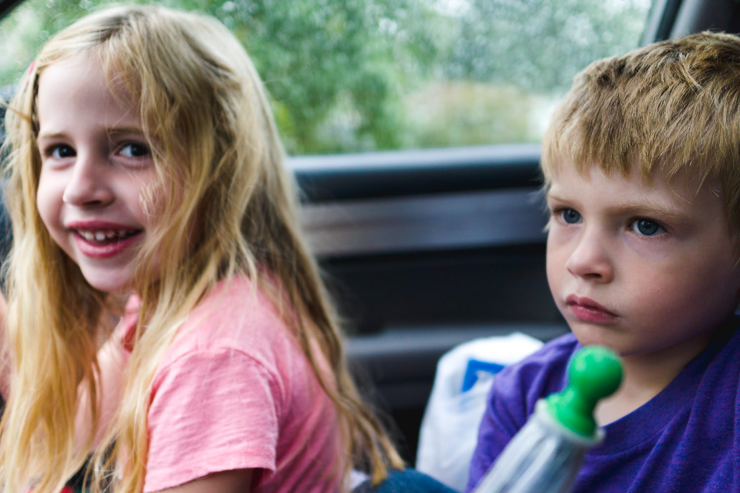 A brother and sister sit next to each other in the car.
