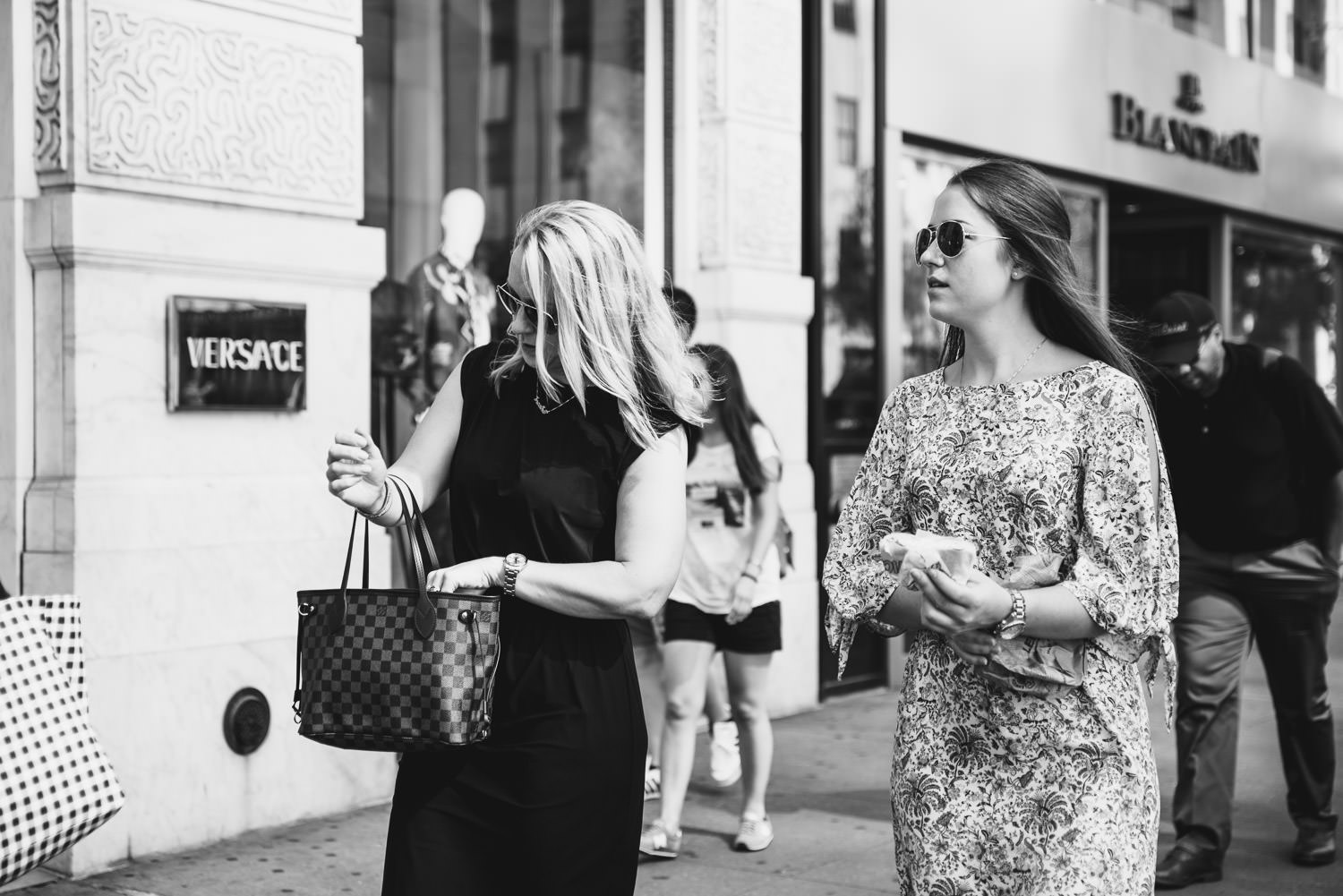 A mother and daughter walk down Fifth Avenue.