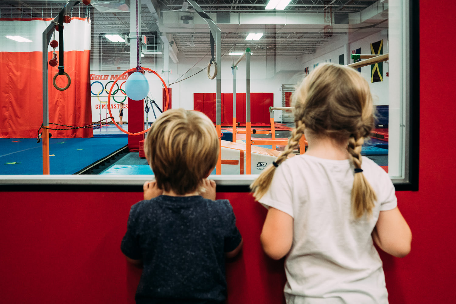 Two children look through the window of a gym.