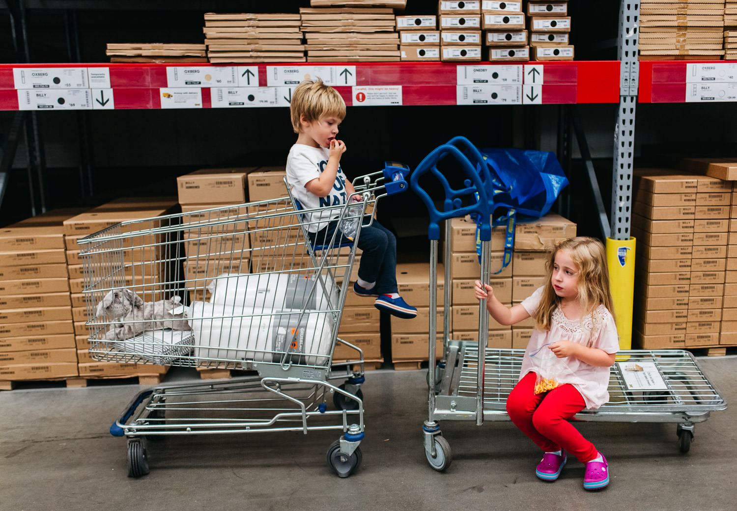 Two children take a break on a cart at IKEA.