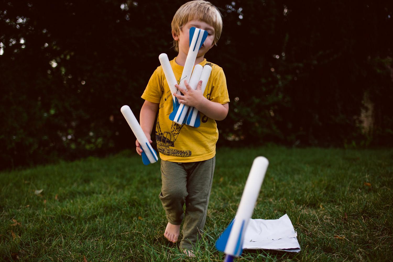 A little boy juggles an armful of stomp rockets.