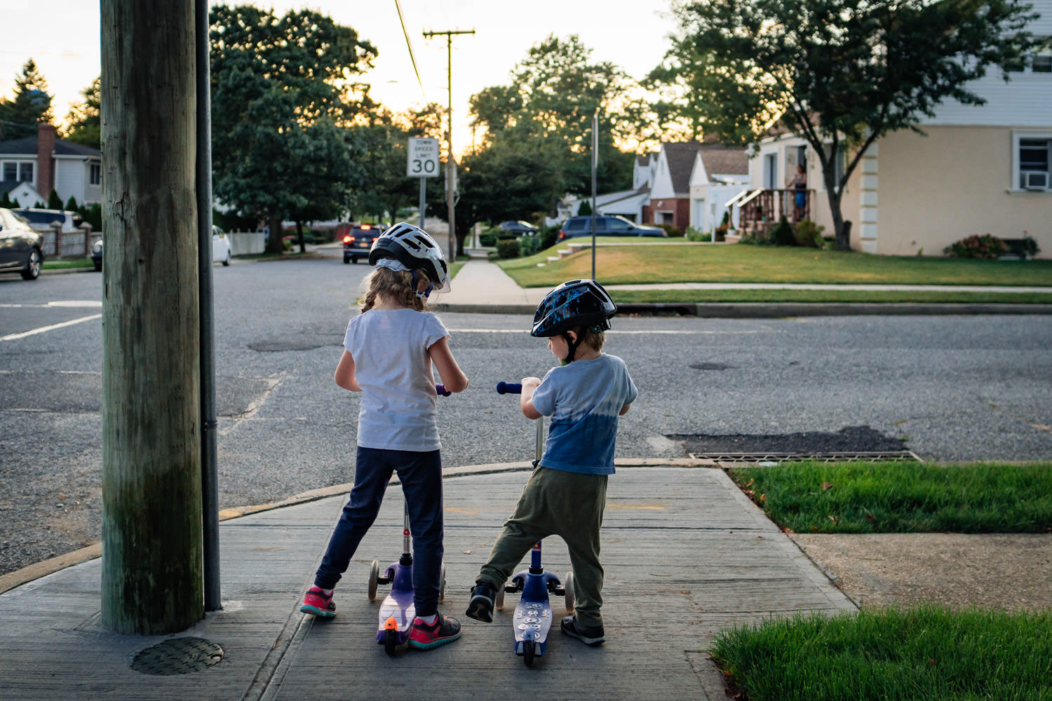 A boy and a girl wait at a street corner with their scooters.