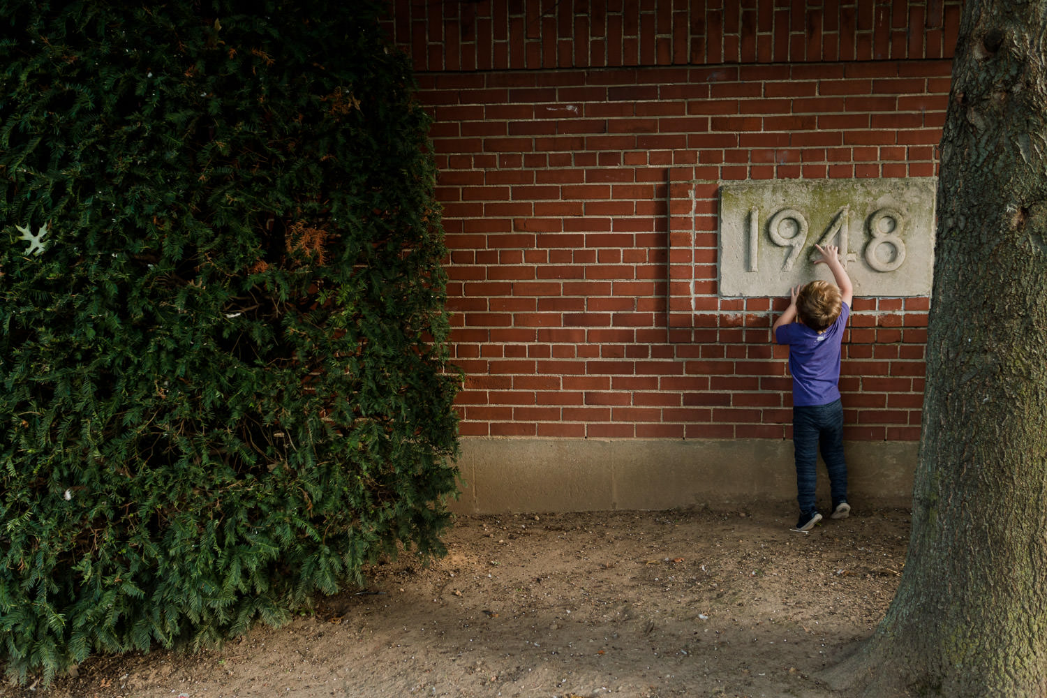 "A little boy points to a plaque on a building that says ""1848""."
