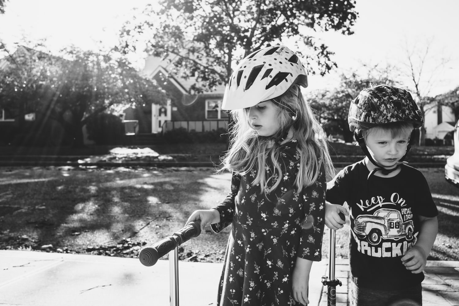 Two children wearing helmets and riding scooters.