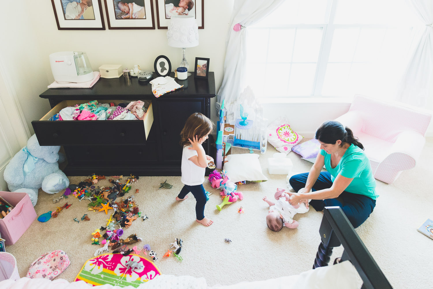 A mom changes her baby's diaper on the kids' bedroom floor.