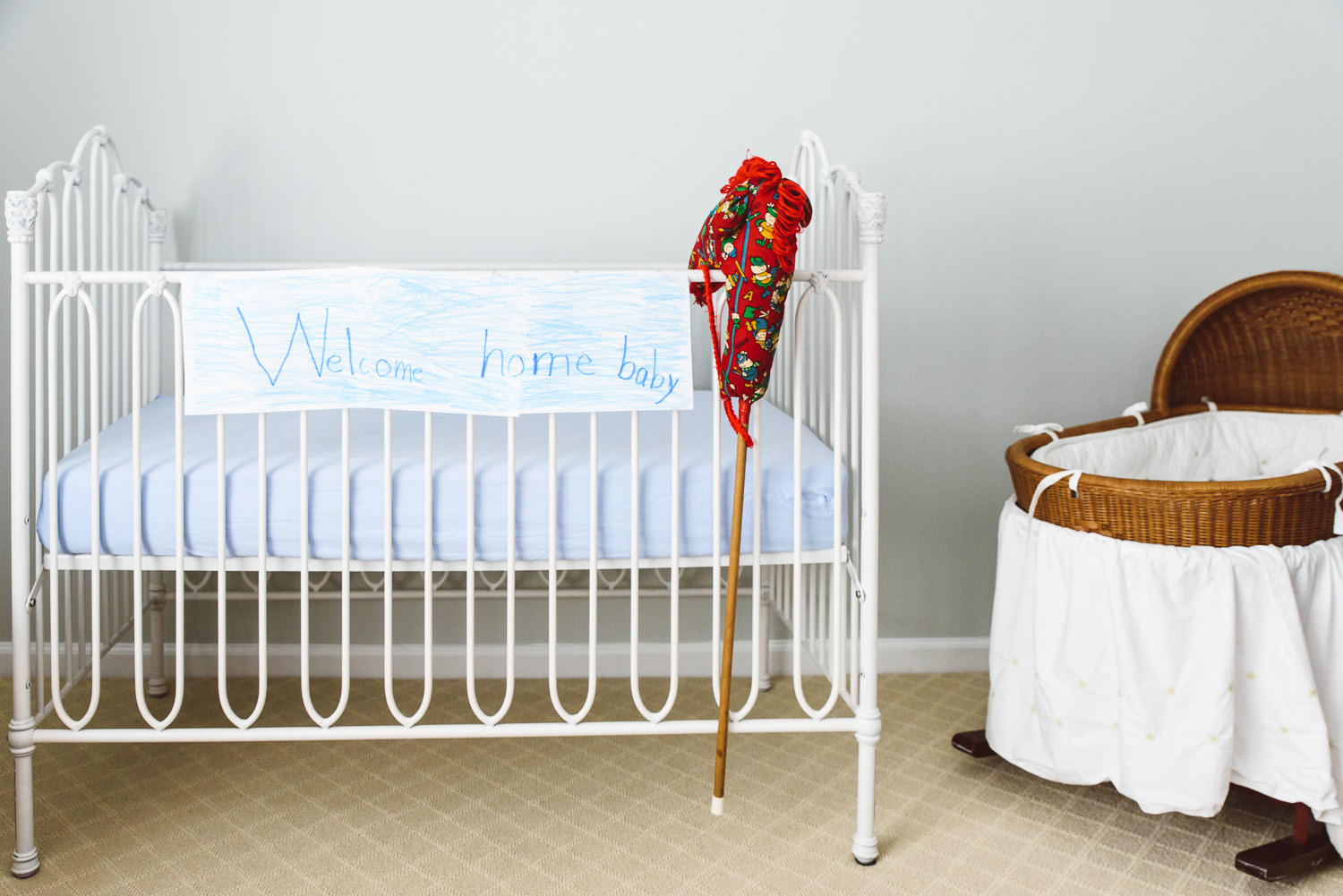 A welcome home baby sign hangs on the side of a crib.