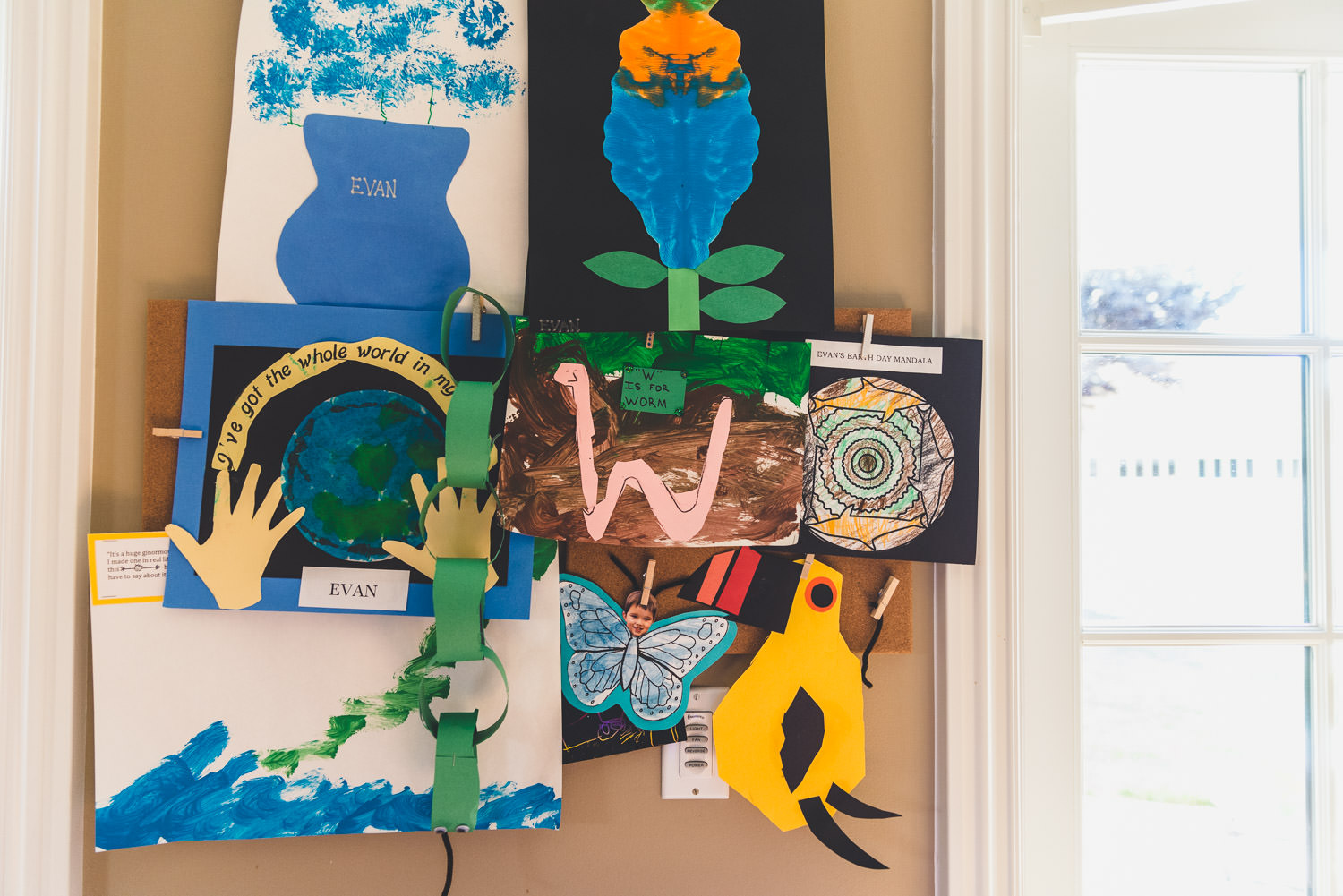 Kids' artwork hangs on the wall of a home.