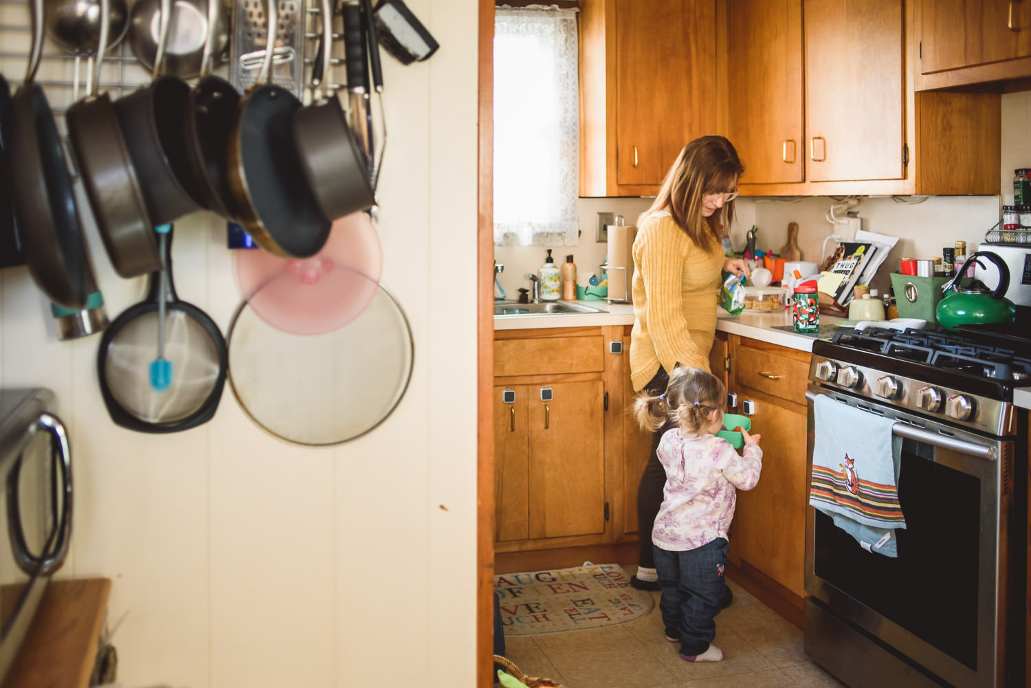 A mother gets her daughter a snack from the kitchen.