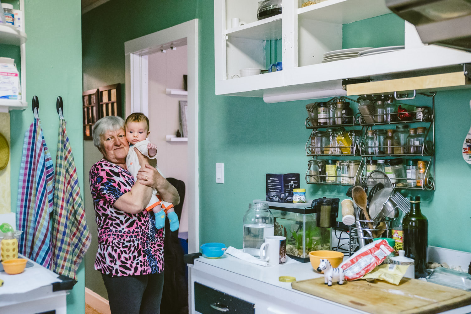 A grandmother holds her grandson in the kitchen.