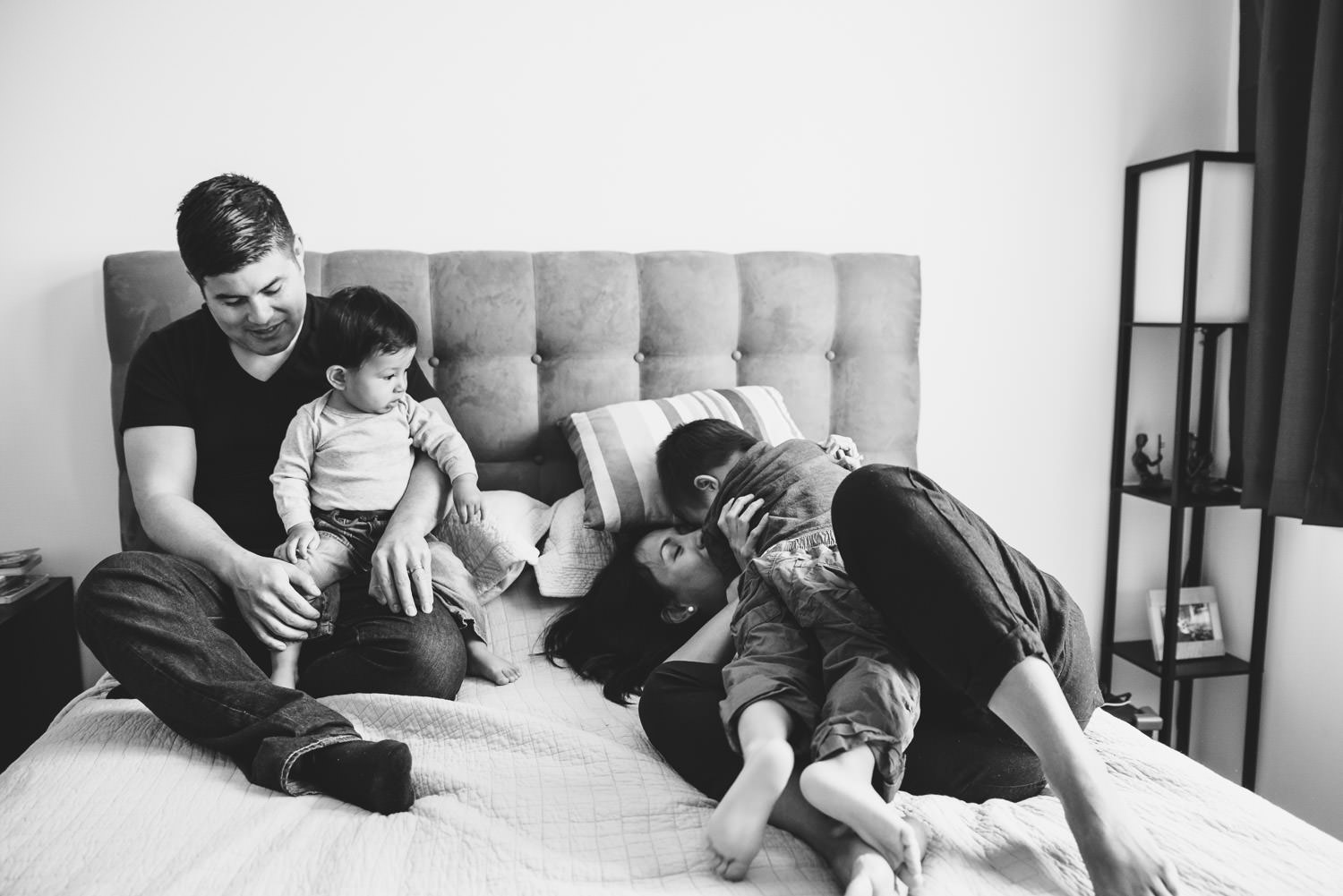 A family cuddles in bed.
