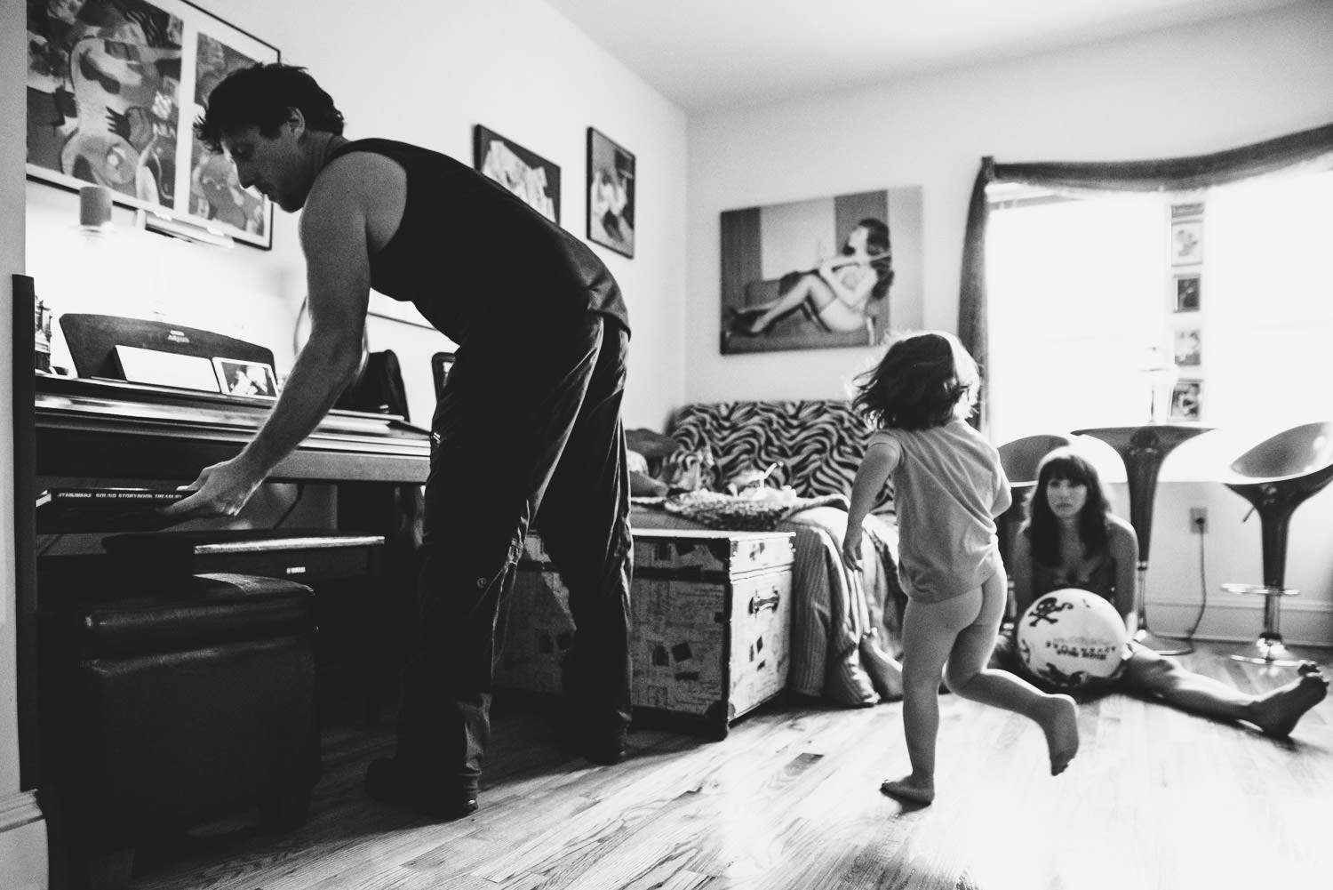 A family plays catch in their living room.