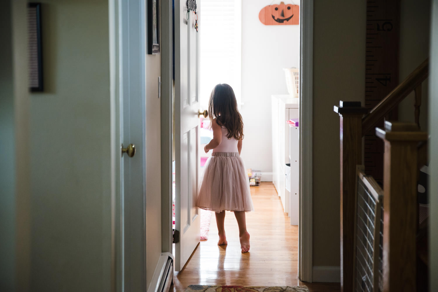 A little girl tiptoes down a hallway.