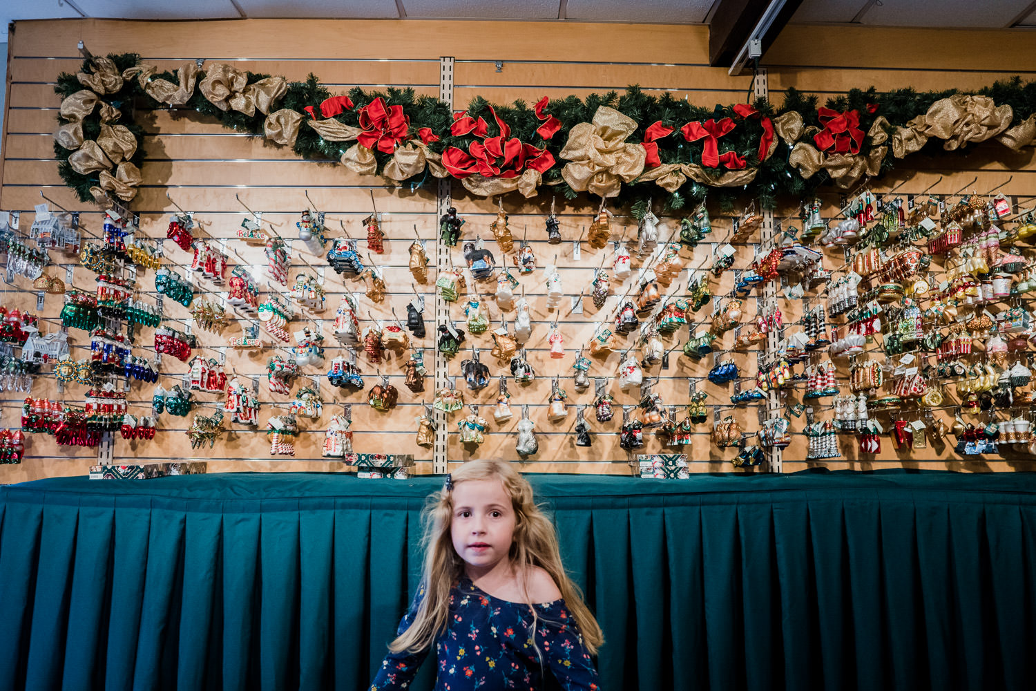 A little girl stands in front of a display of Christmas ornaments.