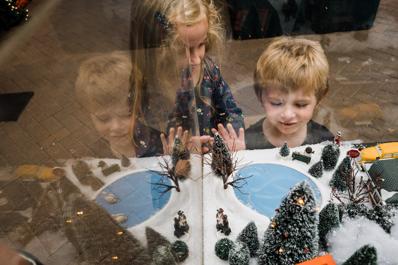Kids look at a holiday miniature display.