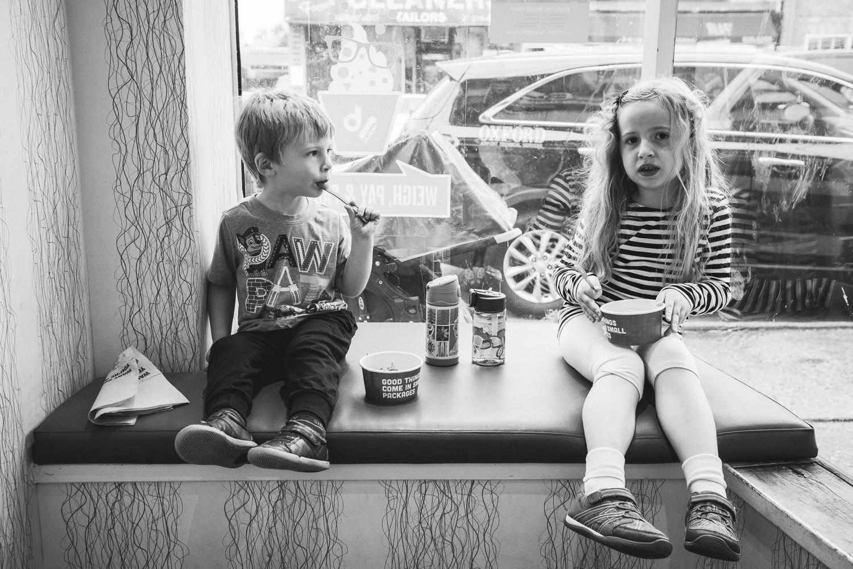 Two kids eat frozen yogurt in the window of the shop.